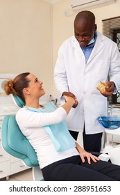 cheerful young woman shaking hands with dentist after teeth checkup