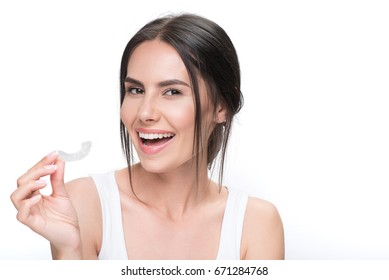 Cheerful young woman showing clear aligner