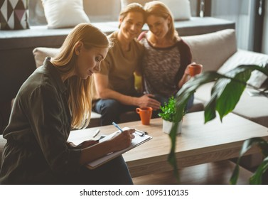 Cheerful young woman is signing agreement about surrogate motherhood. Happy married couple are sitting and smiling in living room