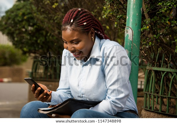 Cheerful young woman sitting alone outdoors in modern urban setting, laughing and looking on cell phone.