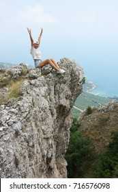 Cheerful young woman sitting with dangling legs on steep cliff.