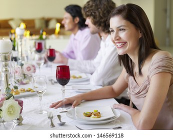 Cheerful young woman sitting with friends at dinner party