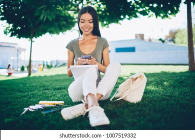 Cheerful young woman sitting on green grass doing homework and chatting with friends via mobile,happy hipster girl share multimedia via smartphone resting in park after lessons in university