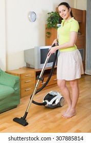 Cheerful young woman in skirt cleaning with vacuum cleaner on parquet floor at home