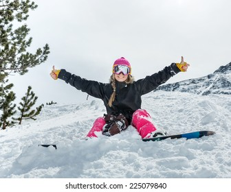 Cheerful young woman snowboarder sitting in the snow wearing a mask shows a sign on the background of beautiful mountains
