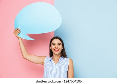 Cheerful young woman standing isolated over two colored background, holding empty speech bubble