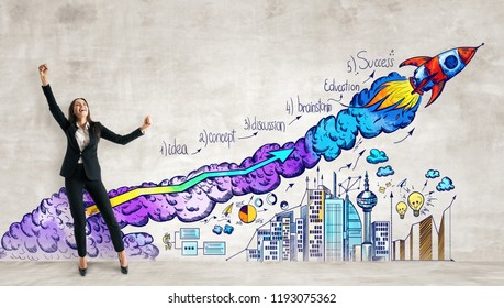 Cheerful young woman standing on concrete wall background with business sketch and launching rocker. Startup and entrepreneurship concept
