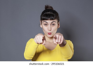cheerful young woman staring at someone with fingers pointing forward with joyful attitude and self-assertion
