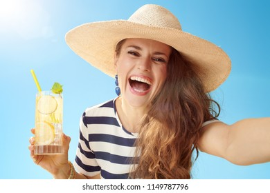 cheerful young woman in straw hat against blue sky with refreshing cocktail taking selfie
