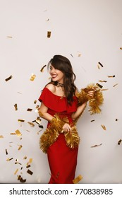 Cheerful young woman in stylish dress posing in golden tinsel and confetti.