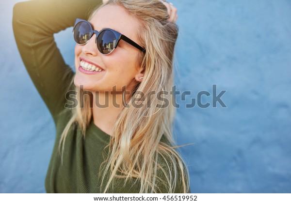 青の背景にサングラスをかけた明るい若い女性。長い髪の美しい女性モデル。