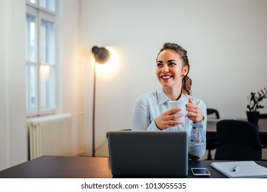 Cheerful young woman taking a break while sitting in the office, in front of a laptop