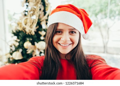 Cheerful young woman taking a Christmas selfie with smartphone.