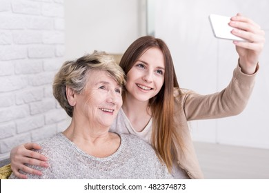 Cheerful young woman taking selfie photo of herself and her grandmother