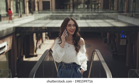 cheerful young woman talking on smartphone while standing with hand in pocket near escalator