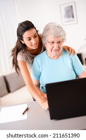 cheerful young woman teaching computer and internet to an elderly person