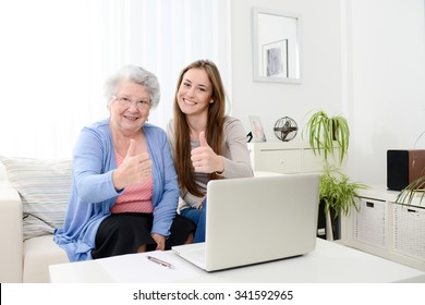 cheerful young woman teaching computer to an old senior woman at home