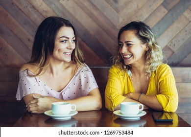 Cheerful young woman telling news to her friend in cafe. Two attractive women drinking coffee and discussing rumors. Gossiping concept