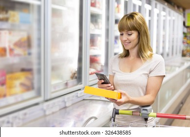 Cheerful young woman texting on mobile phone in supermarket