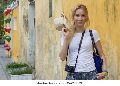 cheerful young woman tourist with camera on street