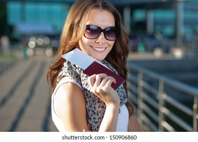 cheerful young woman tourist holding passport and ticket