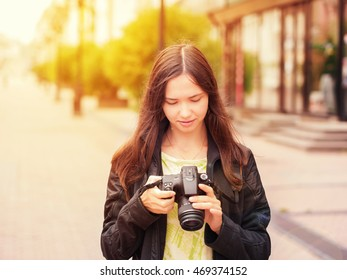 Cheerful young woman tourist watching shots in her dslr camera outdoors. Image with sunkissed effect. Vacation photography travel concept