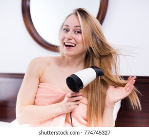cheerful young woman using hairdryer to style her hair after shower 5fbfea4c0