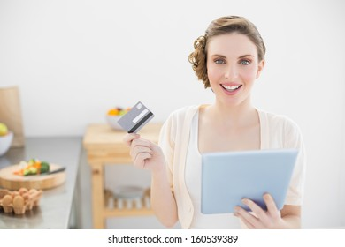 Cheerful young woman using her tablet for home shopping sitting in her kitchen looking at camera