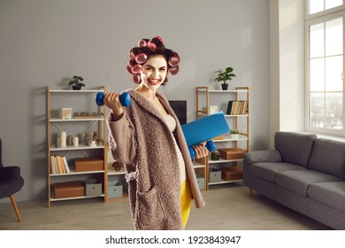 Cheerful young woman wants to keep fit and enjoys fitness exercise at home. Happy smiling housewife in curlers and beauty face mask standing in living-room and holding workout dumbbells and sports mat