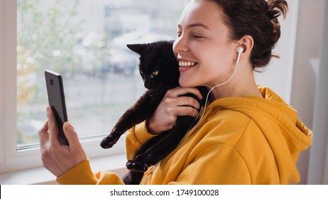 Cheerful young woman wearing headphones holds black pet cat using smartphone for video call, gesturing hi to friend or parent.Caucasian girl in yellow hoodie making selfie,sharing data on social