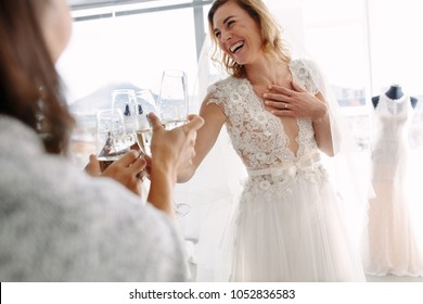 Cheerful young woman in wedding gown toasting champagne with friends in bridal Boutique. Beautiful bride in elegant wedding dress clinking glasses of champagne with her friends.