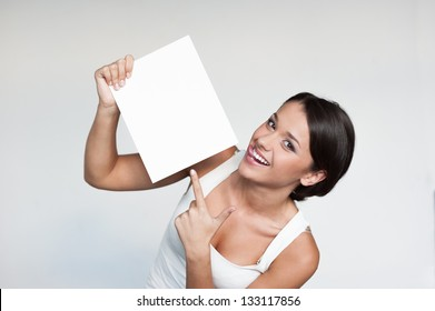 cheerful young woman in white singlet holding sign over gray background