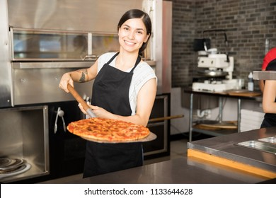 Cheerful young woman working in pizza shop presenting fresh baked pizza over peel standing behind counter