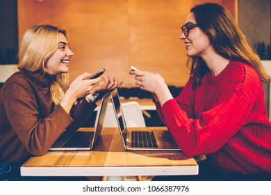 Cheerful young women communicating with each other about great news of successful freelance project,smailing hipster girls  talking to each other while studying and preparing common project together