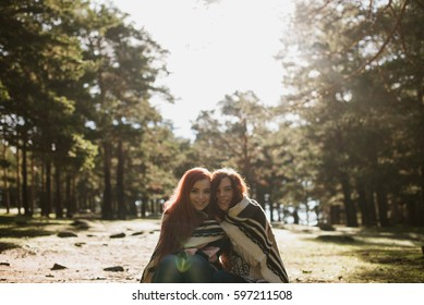 Cheerful young women embracing in plaid in sunny forest meadow.