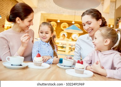 Cheerful young women and their daughters having yummy cupcakes in cafe