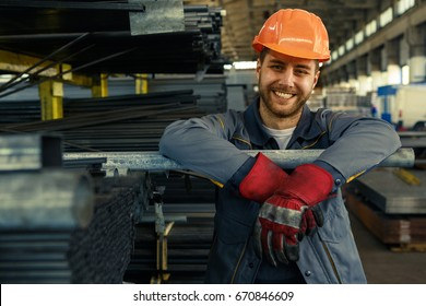 Cheerful young worker in hardhat and uniform smiling to the camera while working at the storage copyspace metal steel metalworking factory production concept