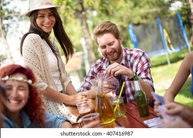 Cheerful youth are perfectly having fun while drinks beer and plays card in nature