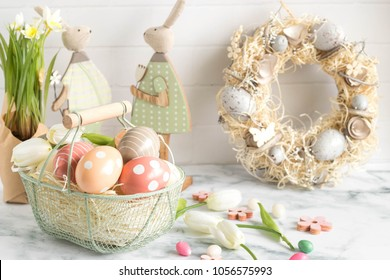 Cheerfull easter home decoration with painted egg basket, rabbits and spring wreath. Colorful easter image with harmony and freshness.
