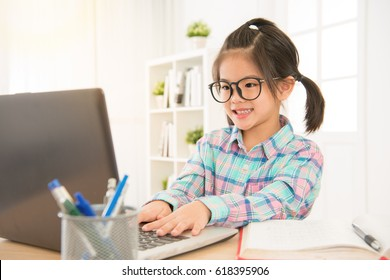 cheerfully cute girl children excited using computer learning schoolwork. asian glasses colorful shirt kid enjoy e-learning in holiday at home.
