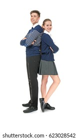 Cheerfully smiling school boy and girl standing back to back on light background