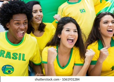 Cheering brazilian soccer fans with jersey an flag at stadium