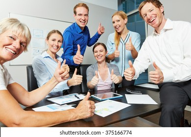 Cheering business team holding many thumbs up in the office during a meeting