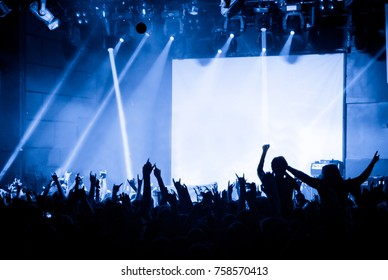 Cheering crowd at concert on the background of stage with a blank white screen