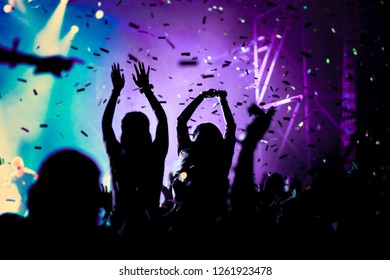 cheering crowd with raised hands and falling confetti at concert - music festival