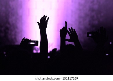 cheering crowd at a rock concert.silhouettes of hands up.purple filter added