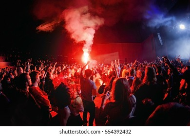 Cheering crowd silhouette and fire pyrotechnic on a festival. Fans burn red flares at rock concert