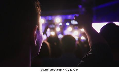Cheering dancing people crowd at rock concert