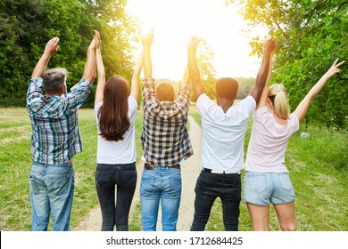 Cheering friends from behind raise their arms in the summer