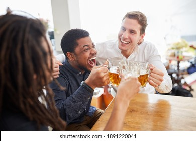 Cheering group of men as friends toasting and drinking beer together